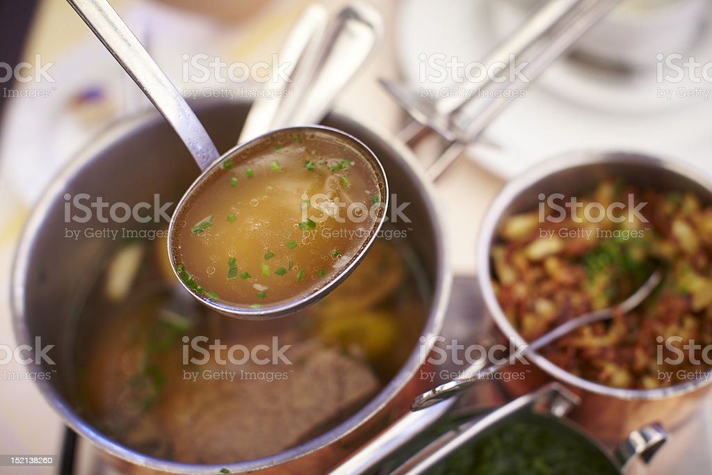 Clear beef soup in a ladle stock photo