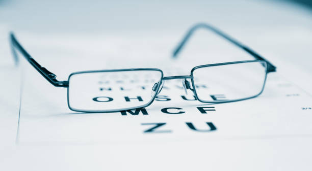clear black modern glasses on a eye sight test chart.. - optometrist stock pictures, royalty-free photos & images