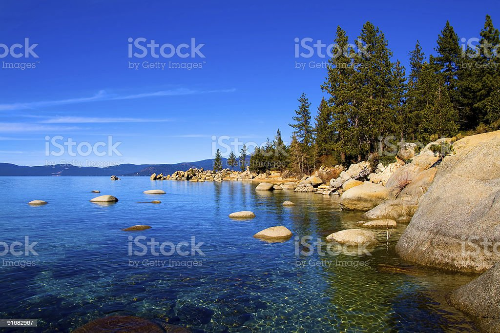 A clear blue lake and rocky shoreline with evergreen trees stock photo