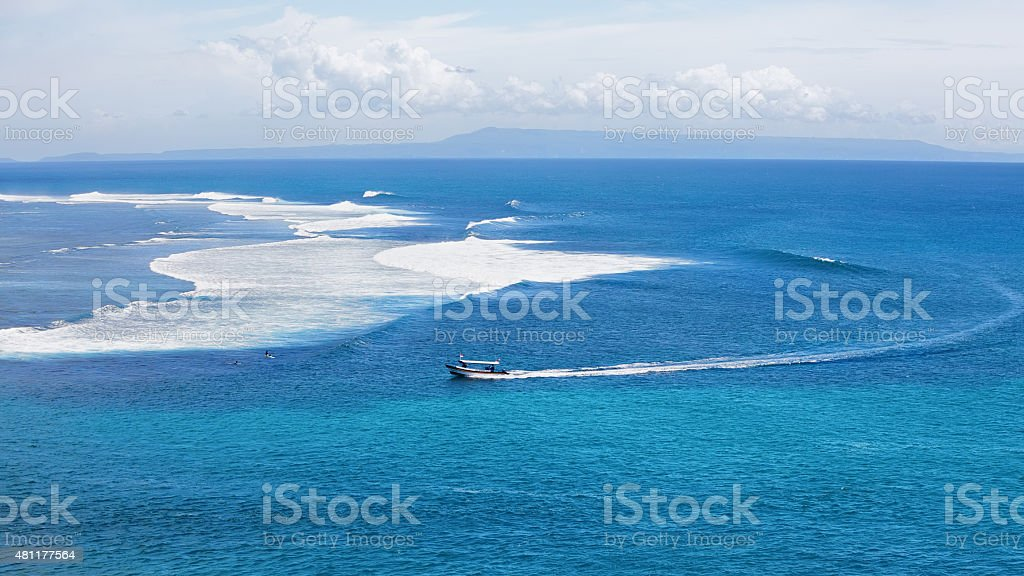 Clear blue ocean with boat and surfers on big waves stock photo