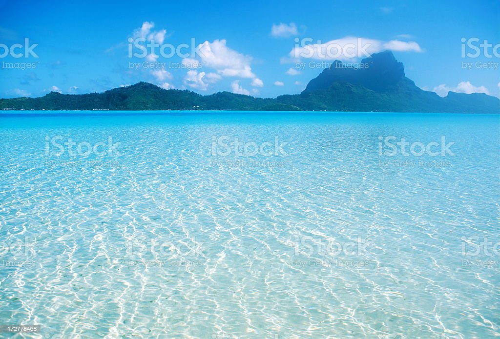 Clear blue ocean with dark mountains in the background stock photo