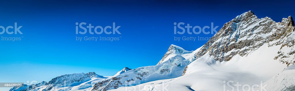 Clear blue skies over snowy Alps mountain peaks Jungfrau Switzerland stock photo