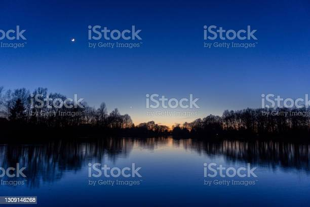 Photo of Clear blue sky after sunset at lake with reflecting silhouettes of trees, venus and crescent moon