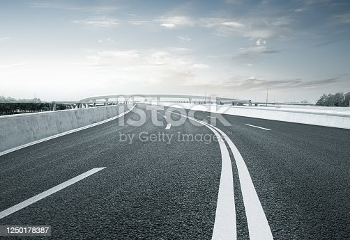94502198 istock photo Clear blue sky and white clouds in the background, highway overpass curved approach bridge 1250178387