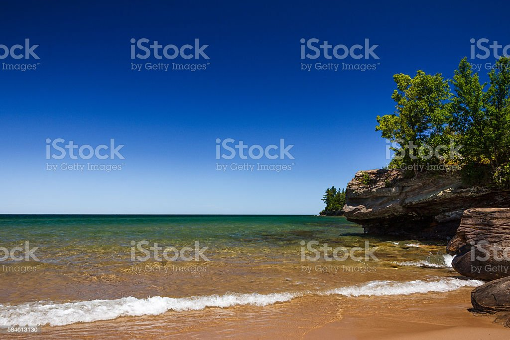 Clear Blue Sky at Sandy Beach with Rocky Coastline stock photo