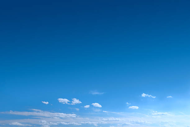 Clear Blue Sky Background With Scattered Clouds A blue sky with clouds at the bottom of image, giving much unimpeded space for copy - Canon 5D MarkII. sky blue stock pictures, royalty-free photos & images