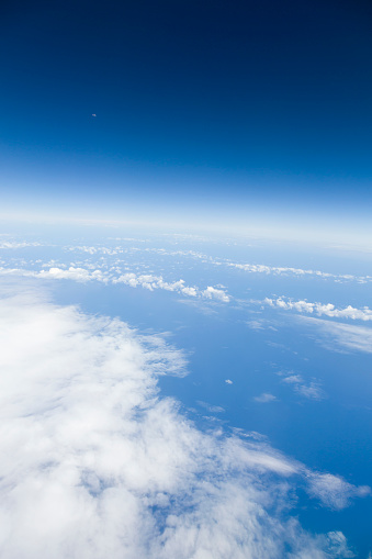 621114928 istock photo Clear blue sky, moon, Atlantic ocean and clouds view from an airplane 1218067607