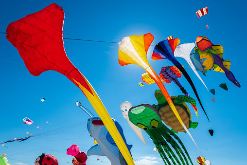 Clear blue sky filled with many different colorful kites