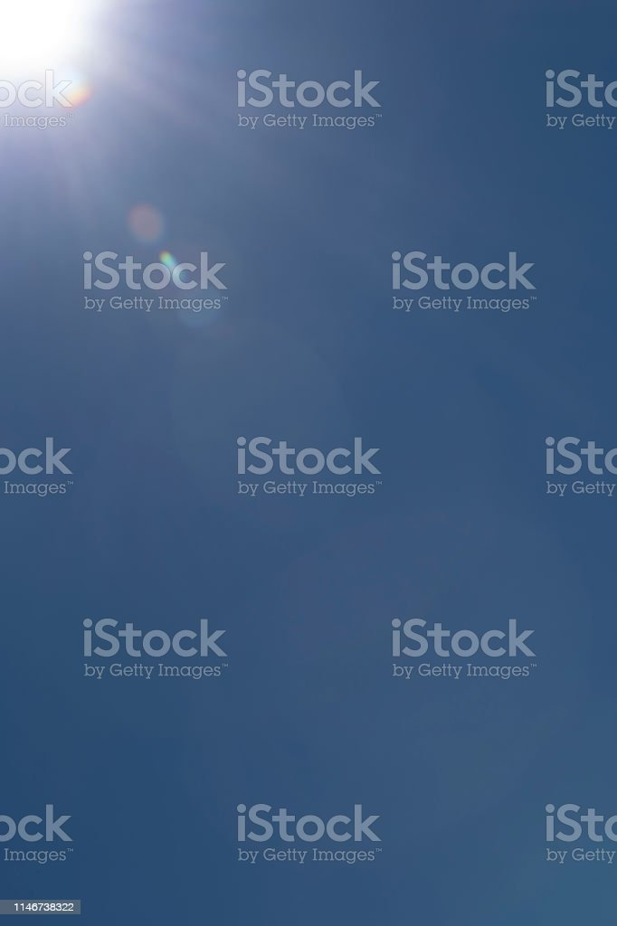 Clear blue sky with the sun and and a deliberate, real lens flare for...