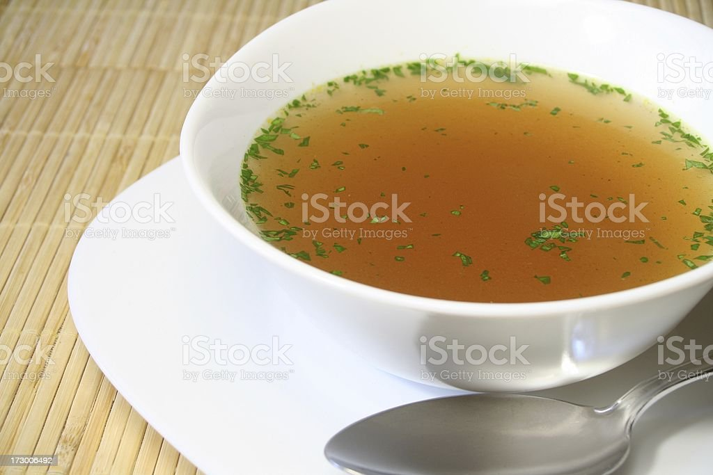 Clear bouillon soup with spoon and plate stock photo