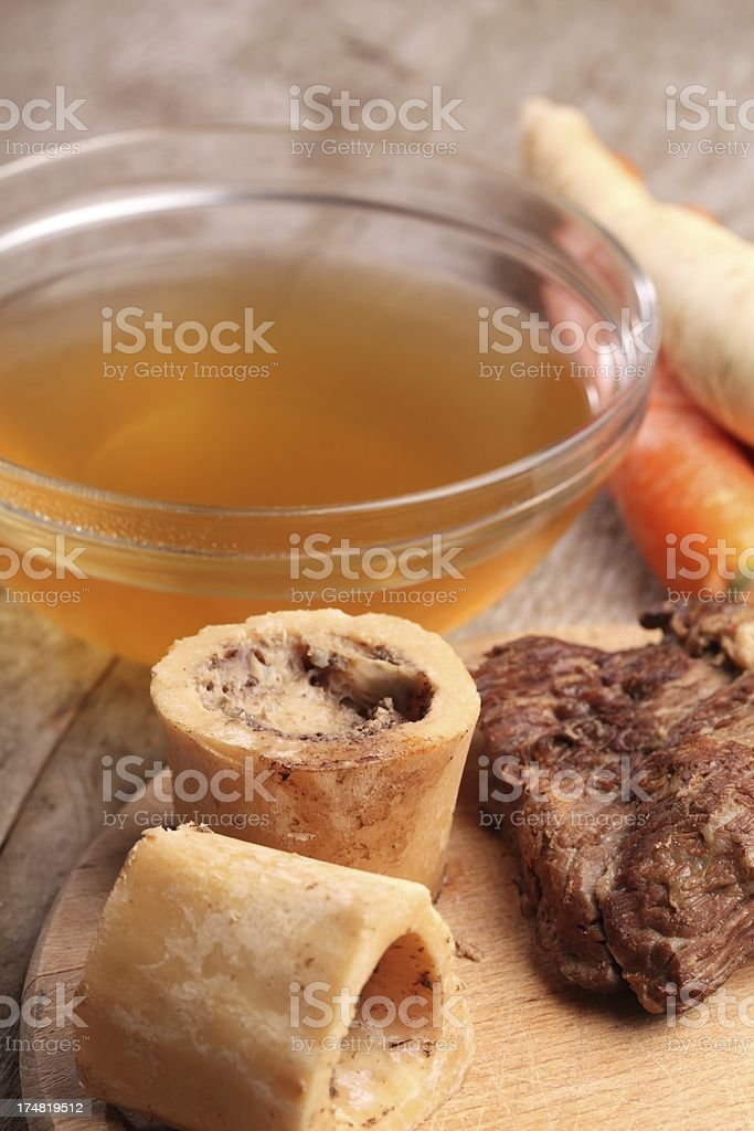 A clear bowl of beef broth and some carrots stock photo