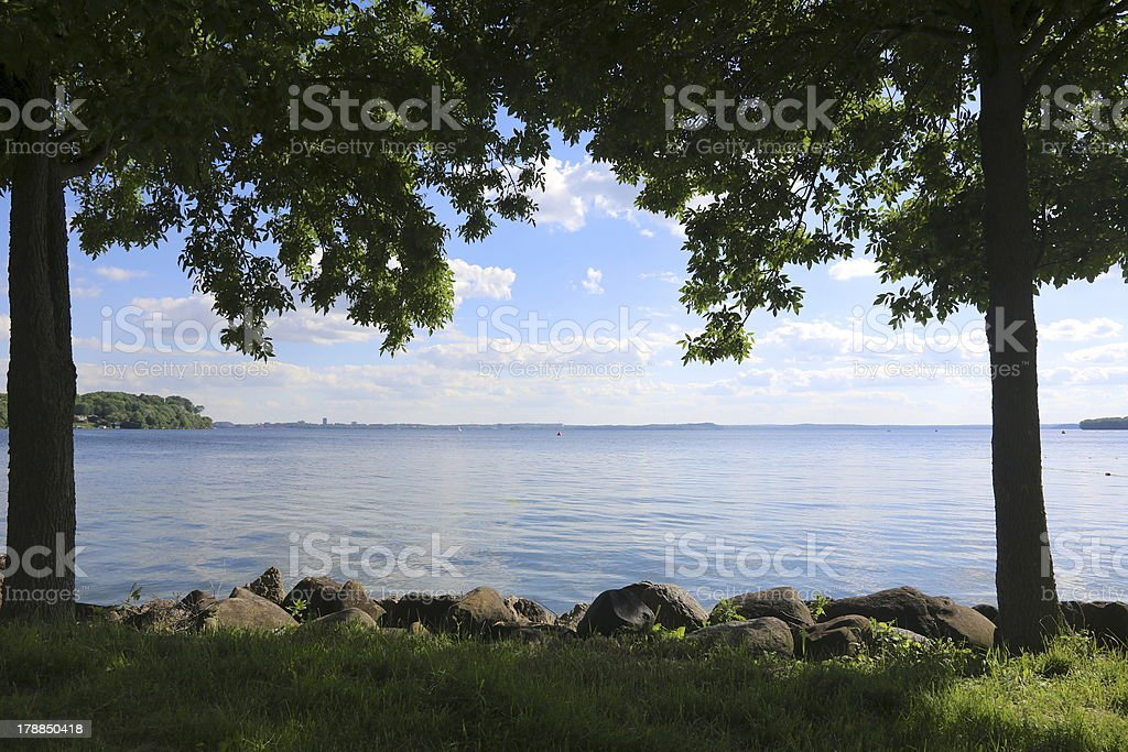 Clear calm lake framed by trees at dusk royalty-free stock photo