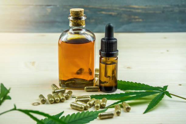 Clear CBD Cannabidiol capsules and cannabis oil on wooden table stock photo