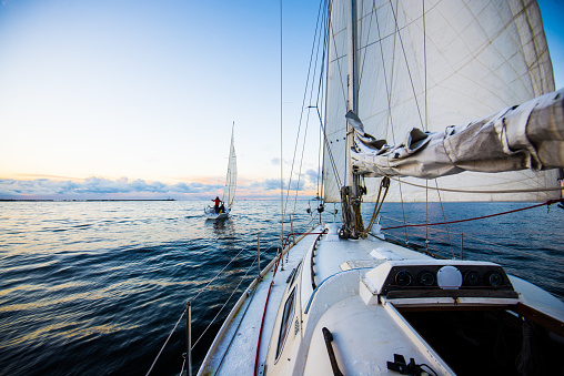 Clear evening sky at sunset. Two yachts sailing. A view from the deck to the bow and sails, close-up. Baltic sea, Latvia