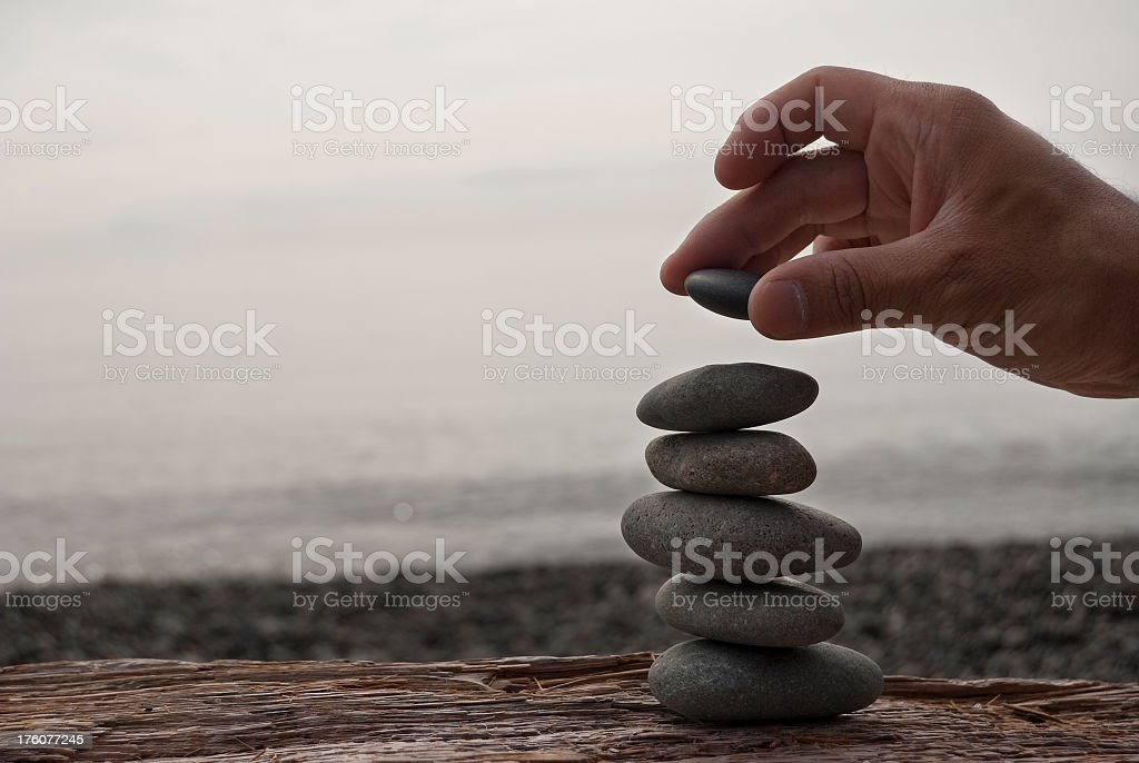 Clear foreground picture of a hand stacking rocks stock photo