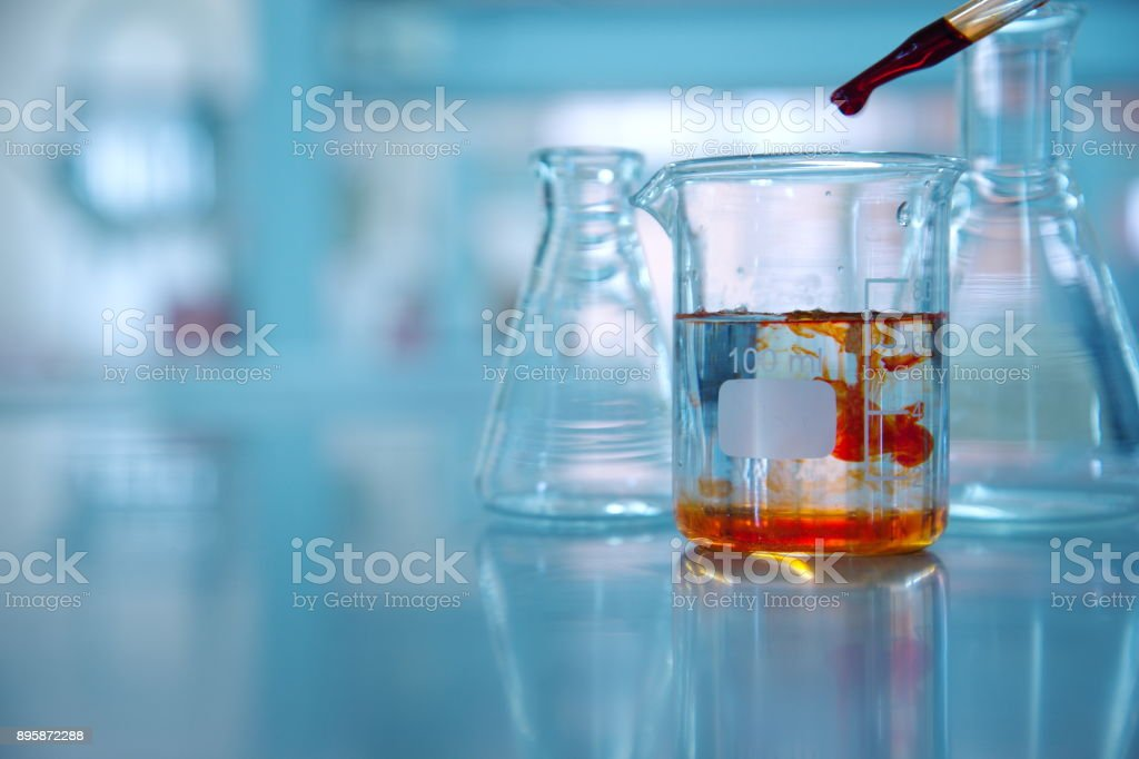 clear glass beaker with orange drop solution in science laboratory background stock photo