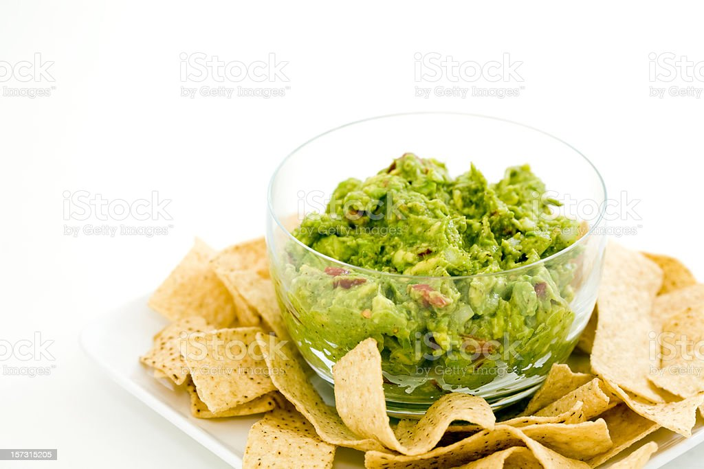 A clear glass bowl of guacamole surrounded by tortilla chips stock photo