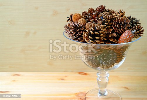 Clear glass compote full of various type and size of natural dry pine cones on wooden background, with free space for text or design