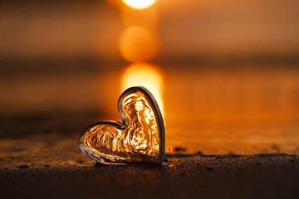 clear glass heart on  sand beach with sunrise sun light stock photo