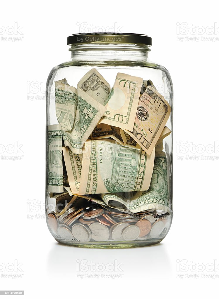 A clear glass jar filled with cash and coins  stock photo
