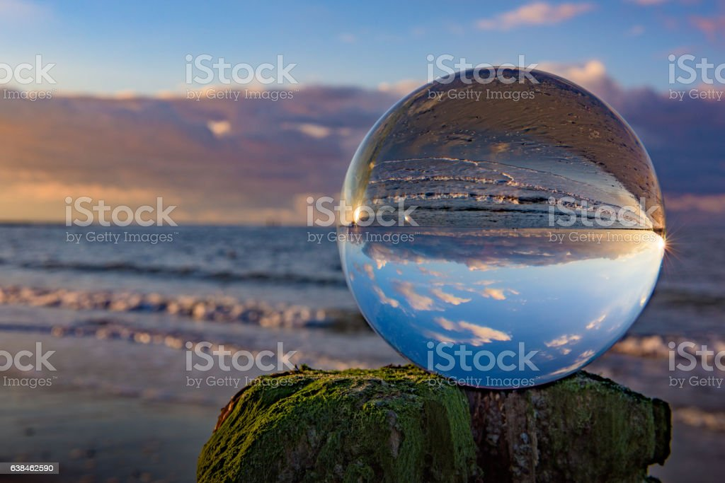 Clear glass sphere at the beach during sunset