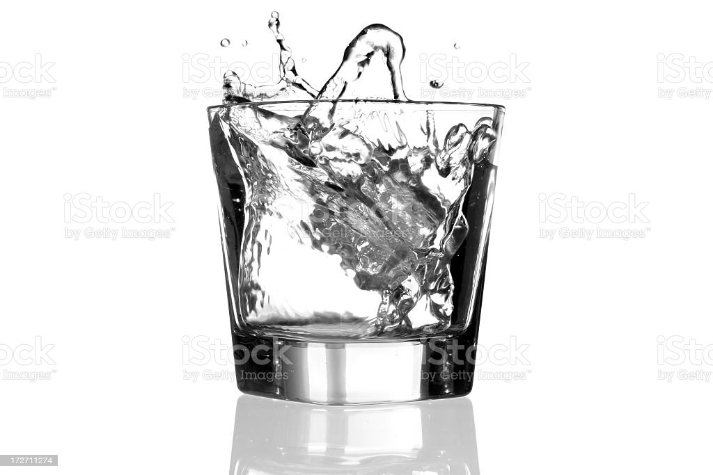 Clear glass with liquid splashing out because of ice stock photo