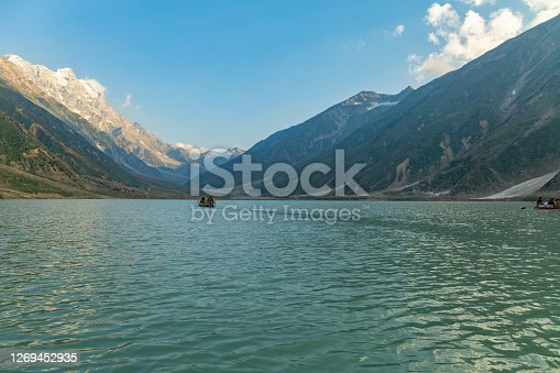 the green water of the lake saif ul malook and mountains with clouds at sunset during the summer season. tourist attraction and famous place of Pakistan in Naran