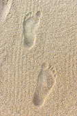 Two clear deep human footprints on sand on beach close-up