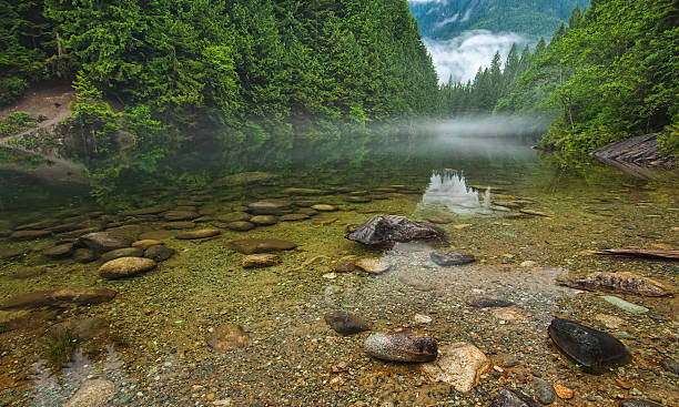 Clear Lake With Rocks and Mist in Distance stock photo
