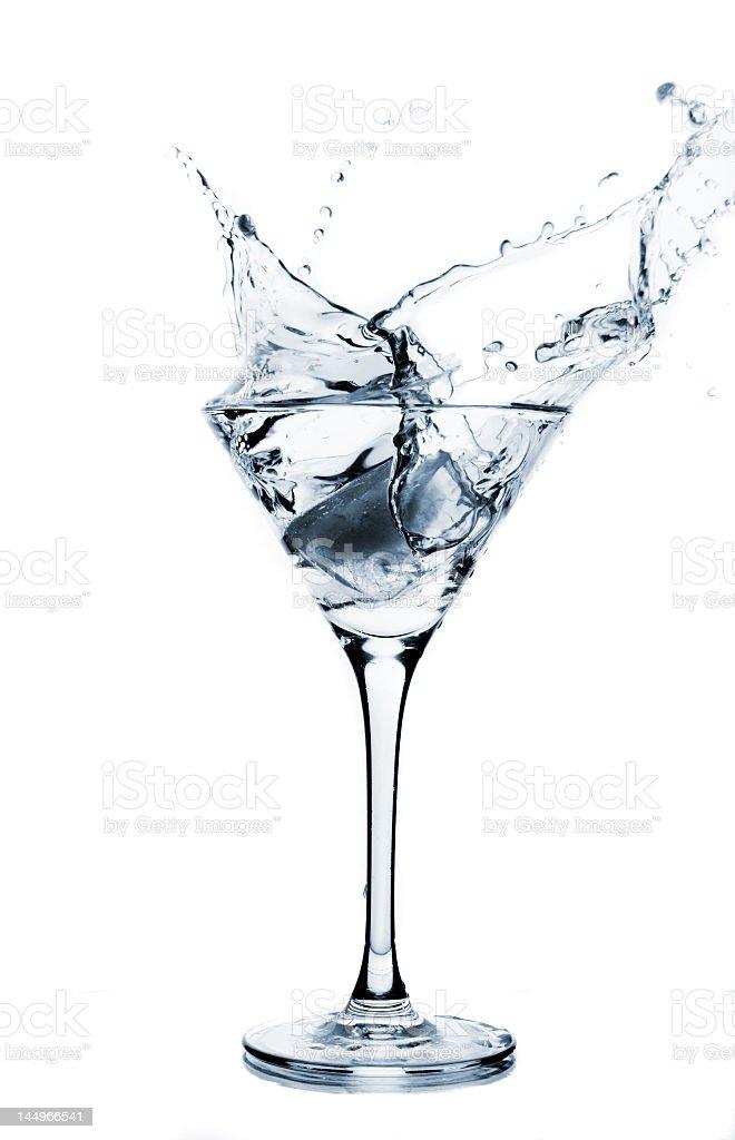 Clear liquid splashing into a martini glass royalty-free stock photo