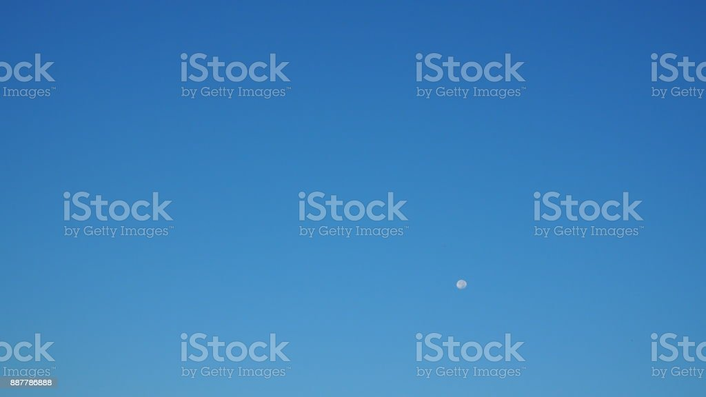 Clear morning blue sky with small white moon floating widescreen background stock photo