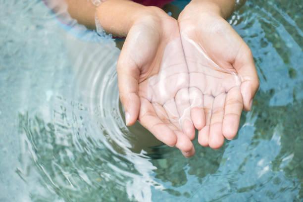oczyścić naturalną wodę w rękach kobiety. - staw woda stojąca zdjęcia i obrazy z banku zdjęć