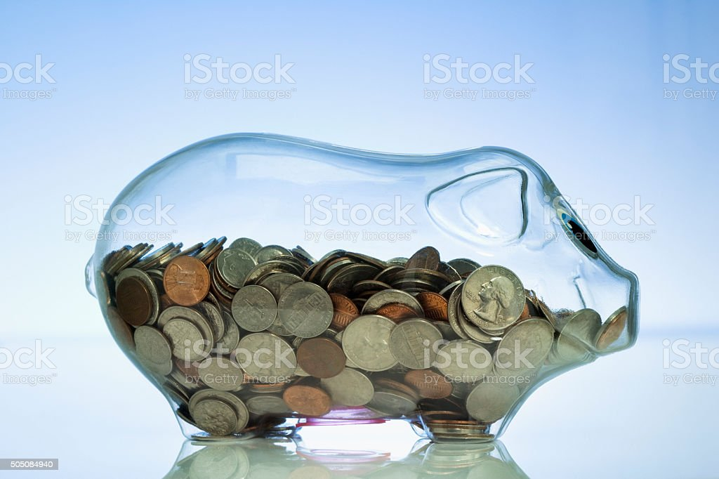 Clear piggy bank halfway filled with coins stock photo
