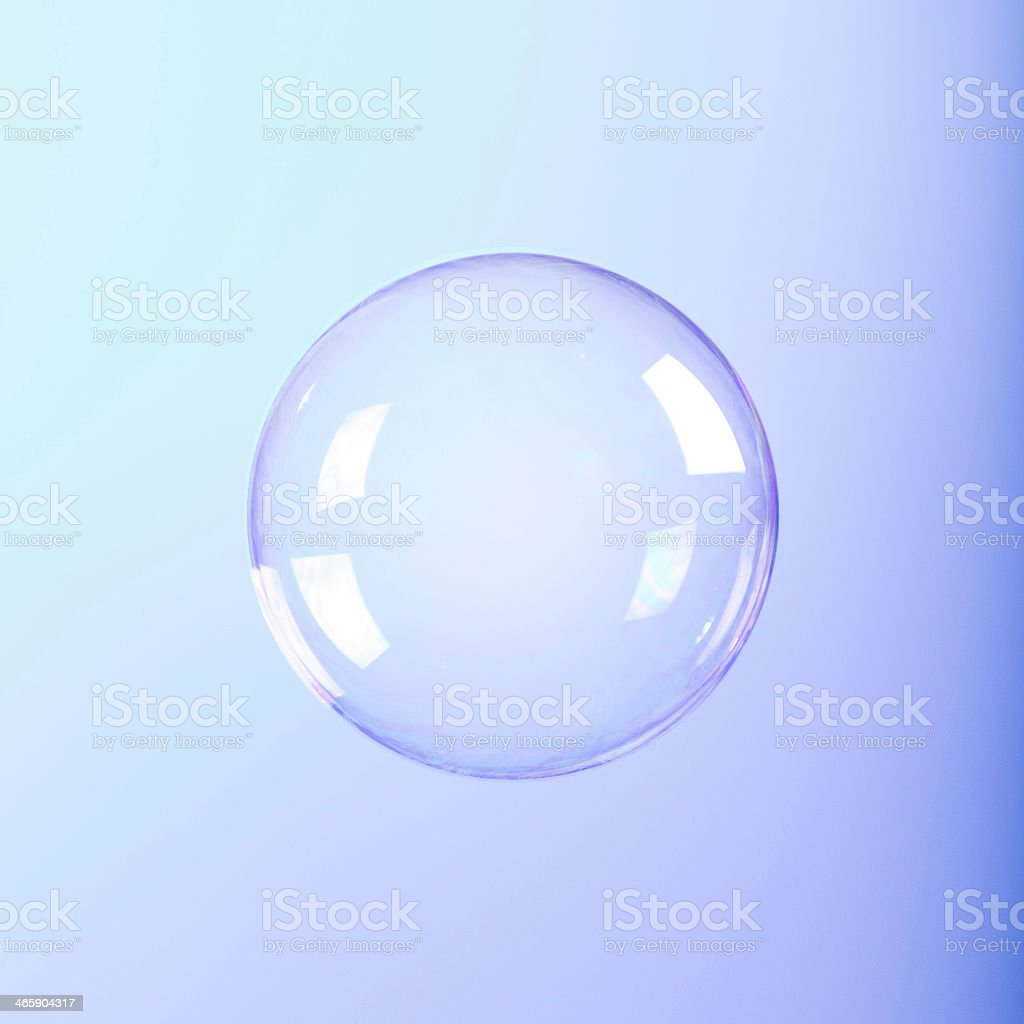 A clear round soap bubble on a bluish-purple background stock photo