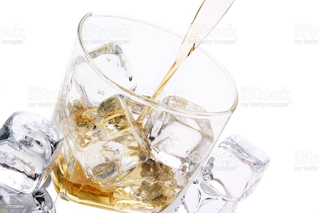 Clear short glass with ice cubes and alcohol being poured royalty-free stock photo