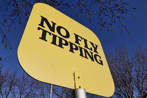 Yellow sign no fly tipping blue sky Clear sign in black on yellow, no fly tipping. Do not fly tip here. Forbidden. whiteway stock pictures, royalty-free photos & images