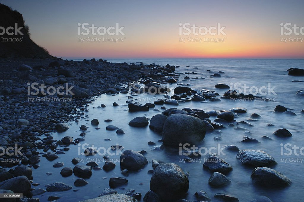 Clear sky after sunset at coast with rocks in water royalty-free stock photo