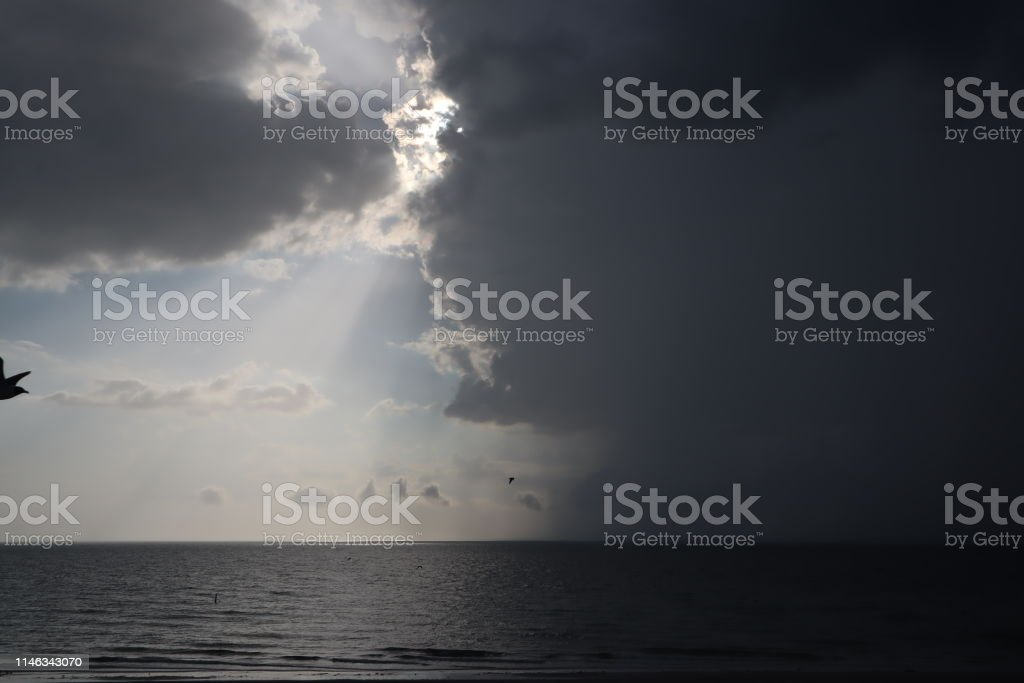 clear sky and storm clouds on the sea. half the sky is clear, half...