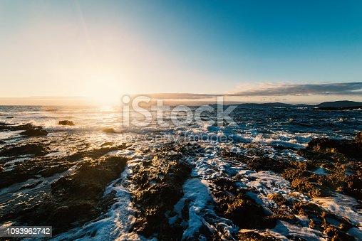 Clear sky over a rocky shore at sunset. Sardinia, Italy