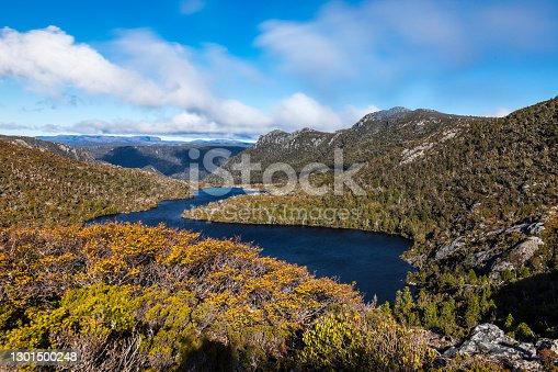 Clear sky over blue lake nestled in the mountains of Tasmania wilderness, Australia