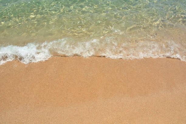 transparente meerwasser, der welle und dem sandstrand entfernt. für design-postkarten und kalender. - roll tide stock-fotos und bilder