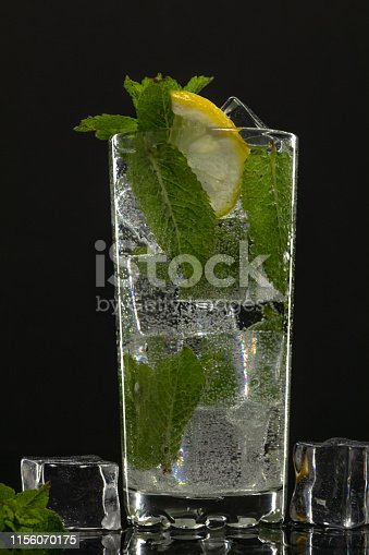 1169153675 istock photo Clear water in glass with green mint leaves and ice cubes on black background 1156070175