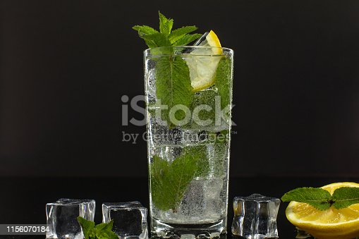 1169153675 istock photo Clear water in glass with green mint leaves and ice cubes on black background 1156070184