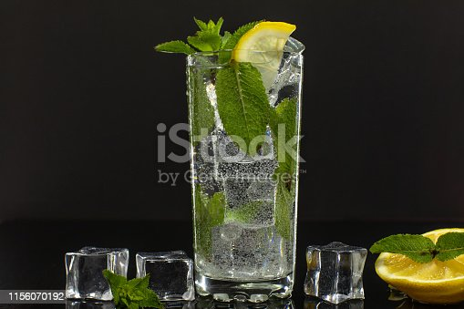 1169153675 istock photo Clear water in glass with green mint leaves and ice cubes on black background 1156070192