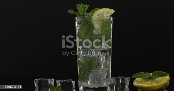 1169153675 istock photo Clear water in glass with green mint leaves and ice cubes on black background 1156070271