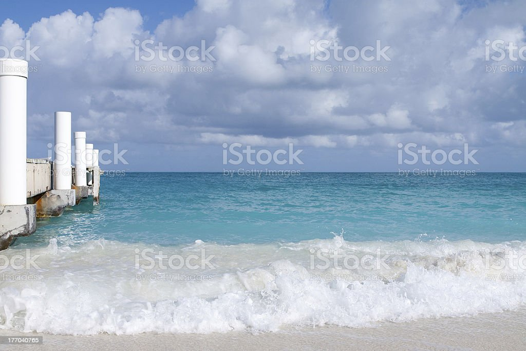Clear wave, white dock, and turqoise sea stock photo
