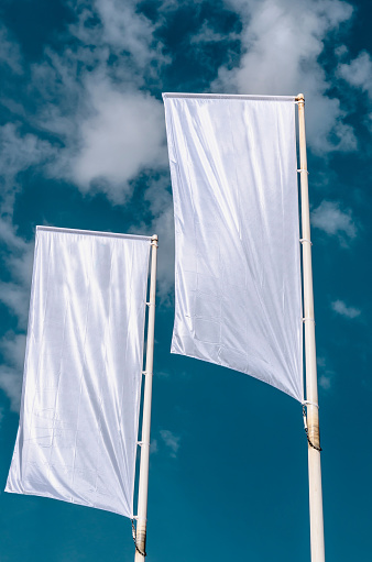 Two cleared advertisement flags waving on the sky