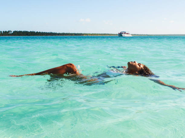 Clearing my minds Young woman is relaxing while floating on crystal clear water of the Caribbean sea. Photo was taken in Caribbean sea, Isla Saona, Dominican Republic. afro caribbean ethnicity stock pictures, royalty-free photos & images