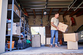 Shot of a man carrying a box in a garage