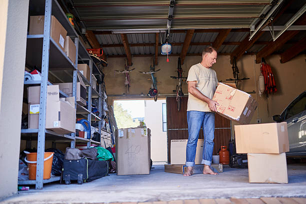 Clearing out some things Shot of a man carrying a box in a garage arrangement stock pictures, royalty-free photos & images